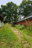 Trayectoria entre el edificio envejecido y el recinto rojo en malas hierbas en d soleada foto de archivo