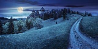 Trayectoria a las ruinas de la fortaleza en la ladera con el bosque en la noche Imágenes de archivo libres de regalías