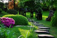 Trayectoria pedregosa adornada con los bonsais en jardín floreciente con luz del sol de la impregnación foto de archivo