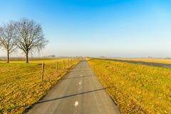 Trayectoria recta larga de la bici en un paisaje holandés del pólder Imágenes de archivo libres de regalías
