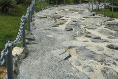 trayectoria Roca-hecha, pavimento hecho de piedras en el cemento Fotos de archivo
