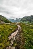 Trayectoria sobre pasto verde en las montañas de Noruega occidental con nieve en las cumbres y un cielo nublado oscuro Imágenes de archivo libres de regalías