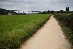 Trayectoria a través del prado, el viaducto en el fondo Fotografía de archivo