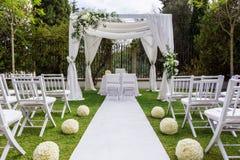 Trayectoria y decoraciones de la boda para los recienes casados En naturaleza en jardín Foto de archivo