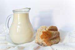 Trayez dans un laitier et un morceau de pain. Photographie stock libre de droits