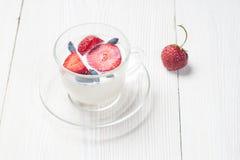 Trayez le dessert de fruit avec les fraises et le chèvrefeuille dans une tasse Photos stock