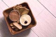 Trayez le gâteau au fromage, décoré des cerises, en verres avec des biscuits dans une cuvette en bois sur une porcelaine pendant  Photo libre de droits