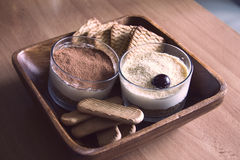 Trayez le gâteau au fromage, décoré des cerises, en verres avec des biscuits dans une cuvette en bois sur une table en bois sur u Photos libres de droits