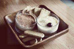 Trayez le gâteau au fromage, décoré des cerises, en verres avec des biscuits dans une cuvette en bois sur une table en bois sur u Images libres de droits