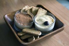 Trayez le gâteau au fromage, décoré des cerises, en verres avec des biscuits dans une cuvette en bois sur une table en bois sur u Image stock