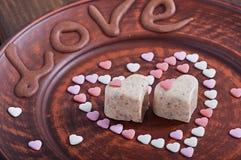 Trayez les bonbons à sésame sous forme de coeur, d'un plat brun avec l'amour d'inscription Image libre de droits