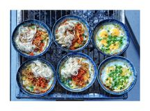 Trays of eggs grilled in bowls stock photos