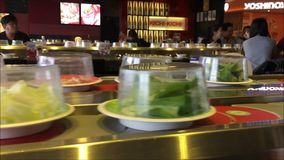 Trays of food moving in line in a Japanese reataurant. Saigon, Vietnam - December 09, 2015: Trays of food moving in line in a Japanese reataurant stock video footage