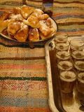 Trays with glasses of tea and fried sweets of the Moroccan kitchen above carpets. Maroc. Trays with glasses of tea and fried sweets of the Moroccan kitchen above Stock Photography