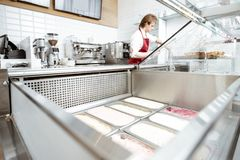 Salesman making ice cream in the pastry shop. Trays with ice cream on the showcase refrigerator with salesman on the background at the pastry shop, wide angle stock photography