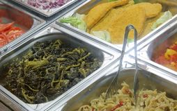 Trays of the restaurant with many spinach foods and cutlets stock image