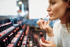 Trazador de líneas de prueba del labio del cliente femenino en tienda del maquillaje imagenes de archivo