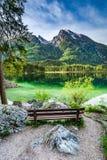 Träbänk på Hitersee sjön i fjällängarna Royaltyfri Fotografi