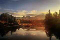 Štrbské Pleso lake. Štrbské Pleso at sunrise, with the High Tatras mountains reflected in the water Stock Image