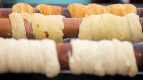 Trdelnik delizioso che brunisce sui bastoni di legno alla cucina ad alta temperatura e ceca stock footage