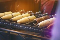 Trdelnik o el trdlo es dulce checo tradicional La mano de la mujer mantiene trdlo la calle de Praga Comida de la calle fotografía de archivo libre de regalías