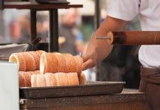 Trdelnik - pâtisserie douce chaude tchèque traditionnelle cuite au four sur un bâton et vendue dans les rues de Prague Photographie stock