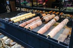 Trdelnik, traditional dessert baked in an open fire wooden stake in Prague Christmas Market. Trdelnik, traditional dessert baked in an open fire wooden stake in royalty free stock images