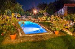 Trädgård med pölen på natten Royaltyfri Foto