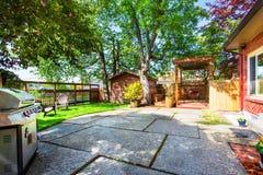 Trädgårddäck med pergolan och den konkreta uteplatsen Arkivfoton