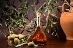 Trdition Crete doprawiająca oliwa z oliwek z spieces rozmaryny i pieprz w lokalnej buteleczce z oliwkami, glinianym dzbankiem i o zdjęcia stock