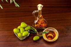 Tradition Crete flavored olive oil with spieces rosemary and pepper, with olives and olive leafs on wooden background. royalty free stock photos