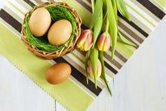Tre ägg i en korg och tulpan Arkivfoto