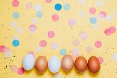 Tre ägg i pappers- rosa rede på den rosa tabellen med konfettier arkivbilder