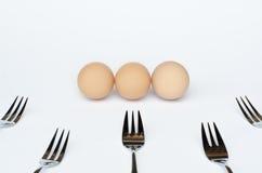Tre ägg och fem gafflar på en vit bakgrund arkivbilder