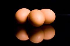 Tre ägg på en svart bakgrund med en reflexion Arkivbild