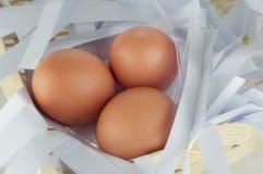 Tre ägg på korg Royaltyfri Foto