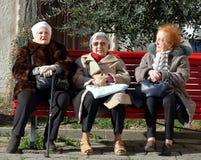 Tre äldre kvinnor som sitter på den röda bänken under trädet i en inre atmosfärisk borggård royaltyfria foton