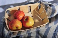 Tre äpplen i en korg på kökshandduken Arkivbild
