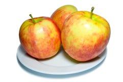 Tre äpplen på en plattacloseup Arkivfoton