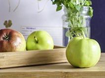 Tre äpplen på en tabell med en träask royaltyfri foto