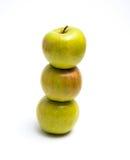 Tre äpplen på en vit bakgrund en på andra Royaltyfria Bilder