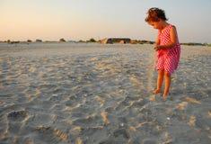 Tre år gammal flicka som spelar med sand arkivfoto