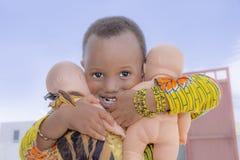 Tre-år-gammal liten flicka som rymmer två dockor i hennes armar Royaltyfri Fotografi