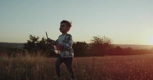 Tre år gammal pojke och hans farsa står upp främsta av kameran i mitt av fältet, på solnedgången lager videofilmer