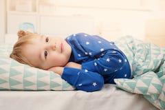 Tre år gammalt barn som ligger i säng Arkivfoto
