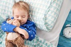 Tre år gammalt barn som sover i säng med ringklockan Fotografering för Bildbyråer