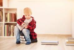 Tre år gammalt barnsammanträde bland böcker hemma Arkivfoton
