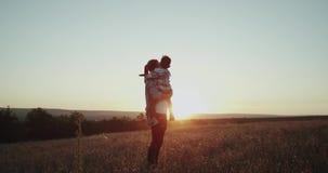 Tre år pojke med hans farsa som tillsammans spenderar en bra tid på solnedgången, kramar och kysser, perfekta ögonblick arkivfilmer