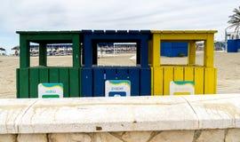 Tre återvinningfack på stranden på Fuengirola, Spanien Arkivbild