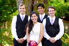 站立与她的三位男傧相的新娘户外在大tre下 免版税库存照片